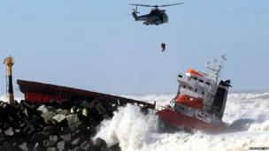 A sailor is lifted to safety from the hold of a ship off south western France