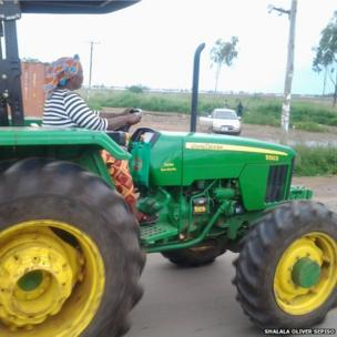 Woman driving tractor in of Lusaka in Zambia