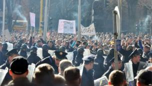 Police stand in front of protesters in the Bosnian town of Tuzla (7 February 2014)