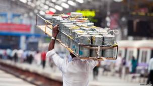 Dabbawala with crate of tiffin tins on his head