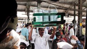 Dabbawala carries a tray of tiffin tins through a crowded railway station.