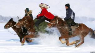 Herdsmen take part in a horse race during a local snow festival in Altay
