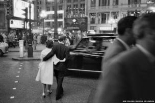 A couple weave across the road in the bustling West End, 1960
