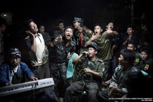 Kachin Independence Army fighters drinking and celebrating at a funeral
