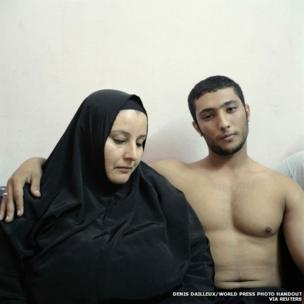 A young Egyptian bodybuilder, posing with his mother in Cairo
