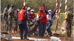 Local Red Cross workers carry a body as they move bodies from a mass grave at a military camp in the 200 villas neighbourhood of Bangui February 17, 2014.