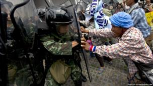 Thai farmers battle with soldiers as they protest the government's repeatedly delayed payments for rice submitted to the pledging scheme at the government's temporary office in Bangkok on 17 February 2014