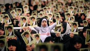A handout picture released by the official website of Iranian Supreme Leader Ayatollah Ali Khamenei on 17 February 2014 shows Iranian women and a girl holding up portraits of him during a meeting in Tehran