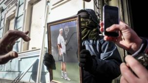Anti-government protesters hold a photo of Ukraine's President Yanukovych as they attack an office of the pro-presidential Party of the Regions in Kiev