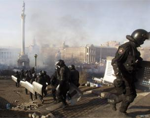 Interior Ministry officers walk in formation as smoke rises above Independence Square in central Kiev