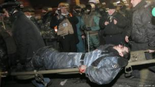 Anti-government protesters carry a wounded policemen during clashes with riot police in Kiev's Independence Square