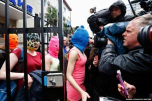 Masked members of Pussy Riot leave a police station in Adler with two other masked women