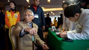 A man selected to attend the family reunions between North and South Koreans is checked by medical staff after arriving at the Hanwha resort in the eastern port city of Sockcho on 19 February 2014