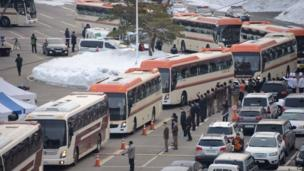 Buses carrying attendees of a family reunion between North and South Korea leave the hotel in the eastern port city of Sokcho on 20 February 2014