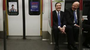 British Chancellor of the Exchequer George Osborne (left) and Hong Kong Mass Transit Railway CEO Jay Walder ride in an underground train in Hong Kong