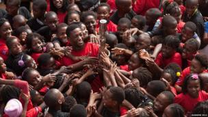 Enthusiastic children reach for the Queen's baton in Matola, Mozambique.