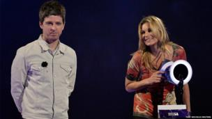 Model Kate Moss accepts the British Male Solo Artist award on behalf of David Bowie as musician Noel Gallagher looks on