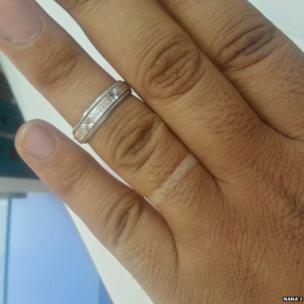 Hand with wedding ring half removed