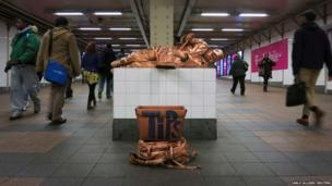 A man performing as a living statue poses for tips in the passage way to the Times Square Shuttle in the Manhattan Borough of New York