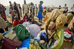 A Ugandan police officer searches the family's luggage at the transit centre near Adjumani.