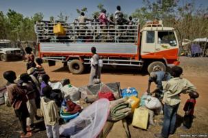 Matiop and his family collect their belongings from the side of the road at Nyumanzi I settlement.