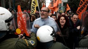 Protesters from the public sector scuffle with police during an anti-austerity rally outside the Finance Ministry in Athens