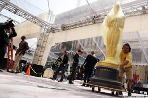 A man pushes an Oscar statue
