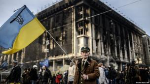 A man stands with a Ukrainian flag on Kiev's Independence square, Ukraine