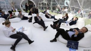 People use their phones in the relaxation area of the 2014 Mobile World Congress in Barcelona