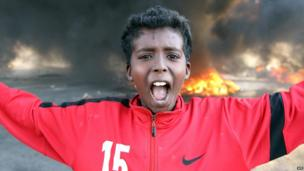 A boy gestures in front of burning tyres in Libya's second city, Benghazi