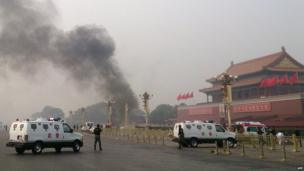 In this file picture taken on 28 October 2013, police cars block off the roads leading into Tiananmen Square as smoke rises into the air after a vehicle crashed in front of Tiananmen Gate in Beijing.