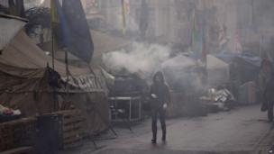 A woman walk past tents erected by protesters opposed to former President Yanukovych in Kiev's Independence Square