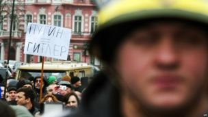 "A demonstrator holds a placard reading ""Putin=Hitler"" as people take part in an anti-war rally in the Ukrainian Black Sea city of Odessa"