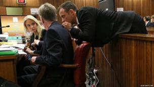 South African Paralympic athlete Oscar Pistorius speaks with his lawyers