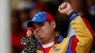 A man holds up a doll of Venezuela's late President Hugo Chavez during a military parade commemorating the one year anniversary of the death of Venezuela's former President Hugo Chavez in Caracas on 5 March, 2014