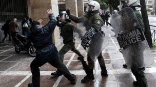 A Greek protester clashes with riot police during a demonstration against austerity measures in Athens