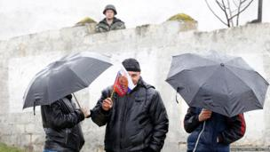Pro-Russian supporters gather outside a Ukrainian military base in the village of Perevalnoye outside Simferopol