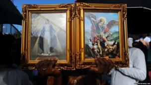A man hold religious images in Port-au-Prince
