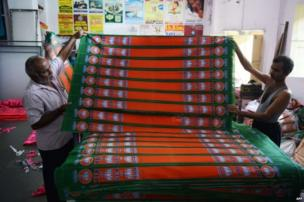 Indian workers make BJP campaign flags at a workshop in Hyderabad.