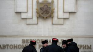 Cossack guards stand in front of Crimea's regional parliament building in Simferopol