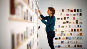 Gloria Cevallos puts up postcards at the Royal College of Art's annual