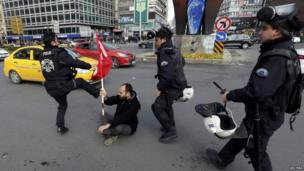 Police officer kicks the flag of an anti-government protester Ankara (12 March 2014)