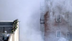 Firefighters take up position on a nearby roof to try to extinguish the blaze