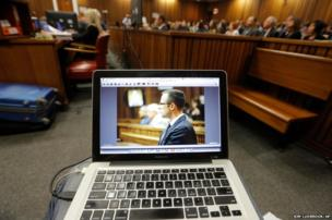 Oscar Pistorius is seen on a laptop as he sits in the dock in court in Pretoria, South Africa