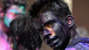 An Indian reveller, covered with coloured powder, celebrates Holi, the Festival of Colours in the old quarters of New Delhi on 17 March 2014