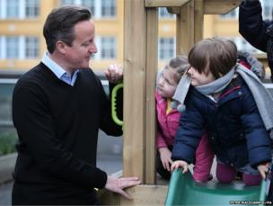 Children look at Prime Minister David Cameron during a visit to the Coin Street nursery in London