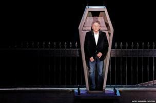 Film director Roman Polanski stands inside a coffin