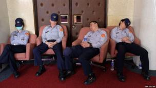 Policemen take a rest during an anti-China demonstration at Parliament in Taipei