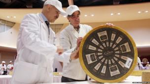 Roberto Castaneda (left) and Max McCalman inspect a wheel of gruyere