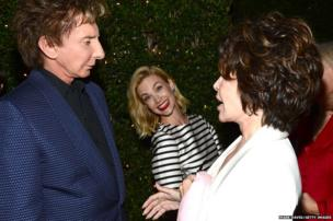 Singer Barry Manilow talks to Carole Bayer Sager as actress January Jones smiles at the photographer